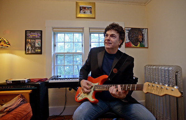 RYAN HUTTON/ Staff photo<br /> Surrounded my music memorabilia, Bob Wolfman strums one of his prize electric guitars (PHOTOGS NOTE, FIND OUT WHAT MODEL GUITAR THAT WAS) in his Middleton home.