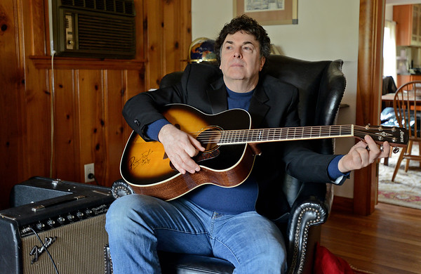 RYAN HUTTON/ Staff photo<br /> Bob Wolfman strums his acoustic guitar in the living room of his Middleton home.