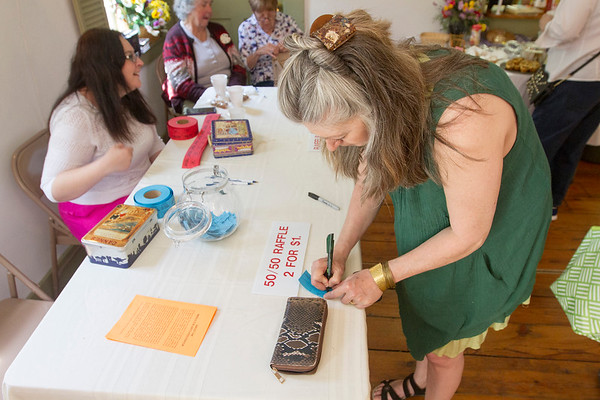 JOE DIFAZIO/ Linda Begin of Derry, New Hampshire fills out raffle tickets at the Middleton Art Association's annual art fair at the Middleton Historical Society. May 14, 2016