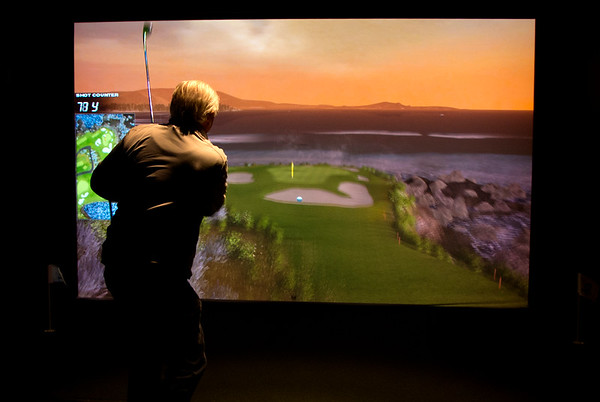 JIM VAIKNORAS/Staff photo Wayne Pasanen owner of the Club House in Middleton plays the 7th hole at Pebble Beach at Sunset on one of the golf simulators