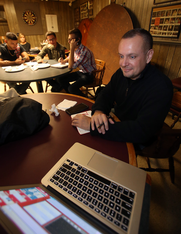 . Republican candidate for state senate, John McDonald, and campaign workers, from left, Mansour Chaya of Methuen, David Morton of Lowell and Curtis Boucher of Lowell, all UML College Republicans, listen to WCAP election coverage at the Bunting Club. (SUN/Julia Malakie)