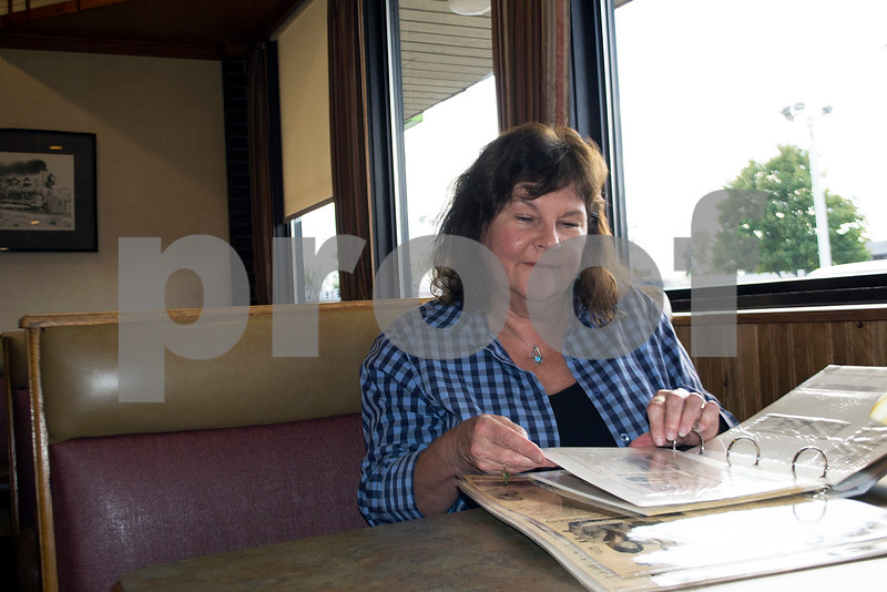 Kathy Siebrasse, former owner and editor of The MidWeek, looks through a scrapbook of newspaper clippings at a DeKalb restaurant. She and her husband, Chuck, owned the paper from 1982 until 2001.
