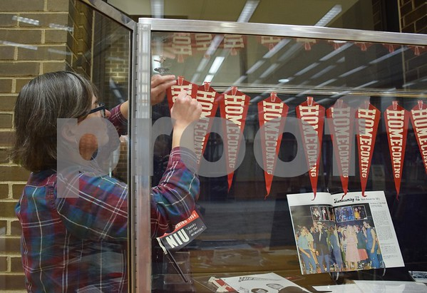 "Northern Illinois University Archives assistant Annie Oelschlager hangs a banner in one of four glass cases that house the Regional History Center's exhibit, ""Homecoming: 111 Years Strong."" The exhibit runs through October in the foyer of Founders Memorial Library. The exhibit is free and open to the public during library hours."