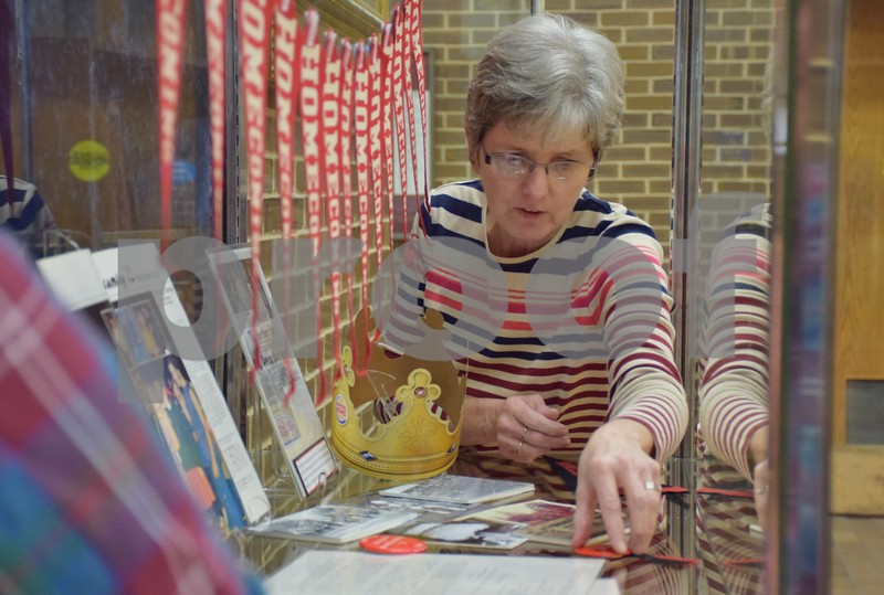 """Assistant University Archivist Margret Abbott decorates one of four glass cases that include items related to Northern Illinois University homecoming history for the Regional History Center's exhibit, """"Homecoming: 111 Years Strong."""" The exhibit runs through October and is  displayed in the foyer of NIU's Founders Memorial Library and the Regional History Center, Room 400. The exhibit is free and open to the public during library hours."""
