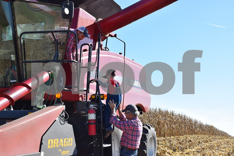 With the help of his grandfather, Ed Czupryna, 5-year-old Jack Krause of Yorkville climbs onto a combine on Vince Faivre's farm in DeKalb on Saturday.