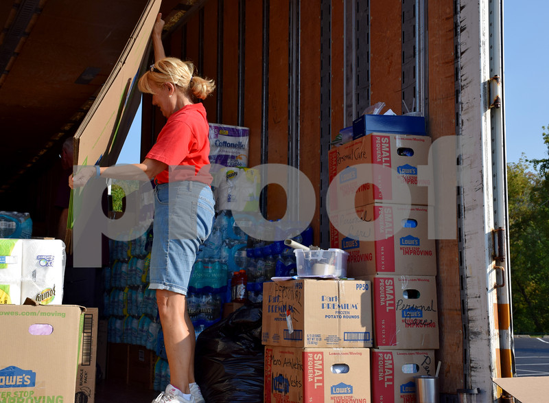 Volunteer Kathy Hall of Genoa moves a box Sept. 15 on the semitrailer full of supplies collected at Crossview Church in DeKalb. The community donated more than 40,000 pounds of nonperishable items to aid in the American Red Cross' Hurricane Harvey relief efforts.