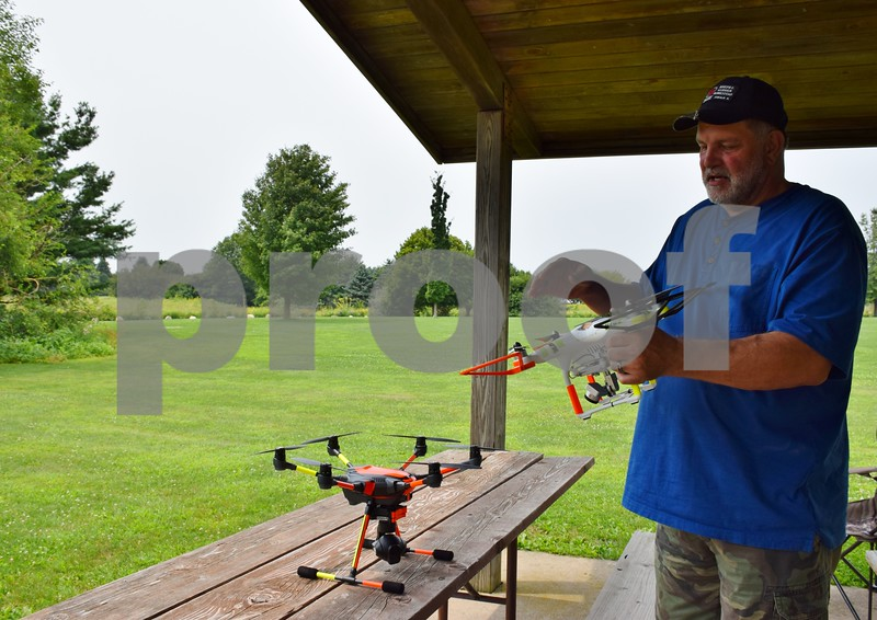 Bob Myers of DeKalb, owner and operator of Hawk Aerial Imagery, performs a pre-flight safety check on his two drones, a Yuneec Typhoon H (left) and a DJI Phantom 3 Professional, before flying them at Afton Forest Preserve on Aug. 3.