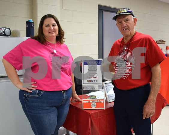 Karen Short (left), a member of the VetsRoll Inc. board of directors, and Air Force veteran Denny Heins pose for a photo in front of the collection box in the veterans room at First United Methodist Church's rummage sale on Saturdat. All of the proceeds from the veterans room will benefit the upcoming 2018 VetsRoll Inc. trip to Washington, D.C.