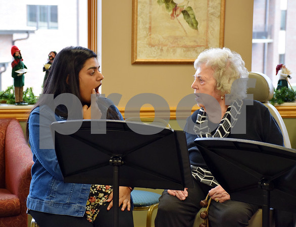 Christina Abraham (left), a Northern Illinois University graduated student in the speech-language pathology program, helps Bridges Choir member Dorothee Aves of DeKalb with vocalizations during a concert Sunday at DeKalb Area Retirement Center – Oak Crest.