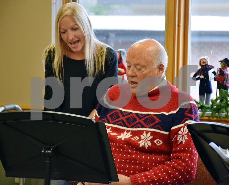 Jamie Mayer (left), Northern Illinois University faculty adviser for the Bridges Choir and associate professor of Allied Health and Communicative Disorders, sings along with choir member Duane Slayton of Sycamore during a concert Sunday at DeKalb Area Retirement Center – Oak Crest.