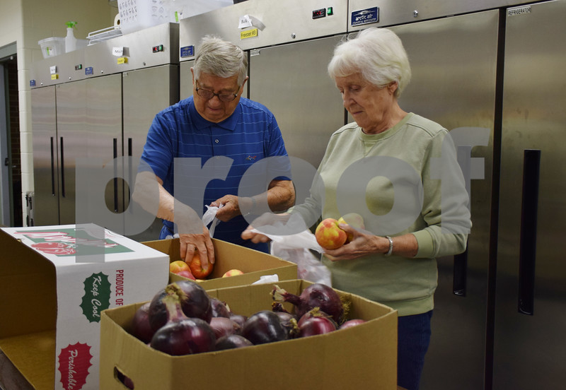 Volunteers Bob and Barb Heimerdinger of DeKalb bag fresh produce at Barb Food Mart in DeKalb. Barb Food Mart received $9,500 from 100+ Women Who Care DeKalb/Sycamore in August 2015 to purchase milk, which freed up other money the pantry used for healthier food options, like fresh produce, cereals with less sugar and spaghetti sauce with less salt.
