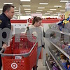 DeKalb Police Patrol Officer Mario Nonnenmann helps Christina Schroyer, 12, shop during the Heroes and Helpers event Sunday at Target in DeKalb. Schroyer had wanted the $60 Fujifilm Instax Mini 9 for months and through Heroes and Helpers, she was able to receive it for Christmas.