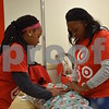 Robin Gibson (right) and her 11-year-old daughter Sydni, both of DeKalb, were two of more than 30 volunteers who helped wrap gifts purchased during the Heroes and Helpers event Sunday at Target in DeKalb.