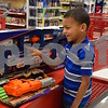 Six-year-old Leandrew Tolliver of DeKalb excitedly looks at his new Nerf Modulus Regulator Gun and reads its description after shopping during the Heroes and Helpers event Sunday at the DeKalb Target store. During the event, Tolliver and his 8-year-old brother Albert each were able choose and take home more than $100 in Christmas presents.