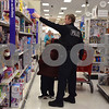 DeKalb Police Detective Sonny Streit helps 9-year-old Tionna Saunders shop during the Heroes and Helpers event Sunday at Target in DeKalb. Thirteen DeKalb police officers volunteered to help with the event, which provided 38 children in DeKalb School District 428 the opportunity to choose and take home more than $100 in Christmas presents each.