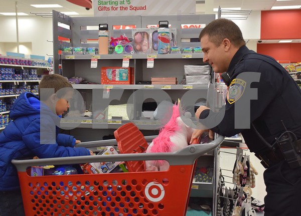 DeKalb Police Deputy Chief John Petragallo talks about Pokémon as he helps 6-year-old Mason Kent shop during the Heroes and Helpers event Sunday at Target in DeKalb. During the event, Kent and his two siblings, 9-year-old Alayna and 4-year-old Jace, each were able choose and take home more than $100 in Christmas presents.