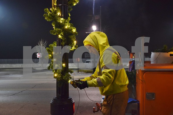 Tanner Sabin, a street maintenance worker with the DeKalb Public Works' Street Operations Division, helps wind garland around a light poles along Lincoln Highway. Sabin said decorating downtown DeKalb put him in the holiday mood and has already decorated his Christmas tree at home with his children.