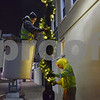 Mark Pumpfrey (left) and Tanner Sabin, workers with the DeKalb Public Works' Street Operations Division, place lighted garland on light poles on Lincoln Highway at 5 a.m. Nov. 14. Public works departments decorate in the early morning hours before work-day traffic begins because their bucket trucks take up space on the streets.