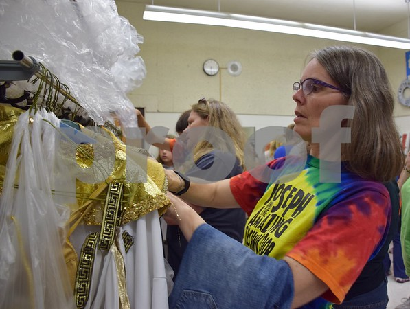 """Parent and volunteer Kathleen Valde of Sycamore organizes the costumes before the rehearsal of Children Community Theatre's Penguin Project production of """"Joseph and the Amazing Technicolor Dreamcoat"""" on Sept. 22."""