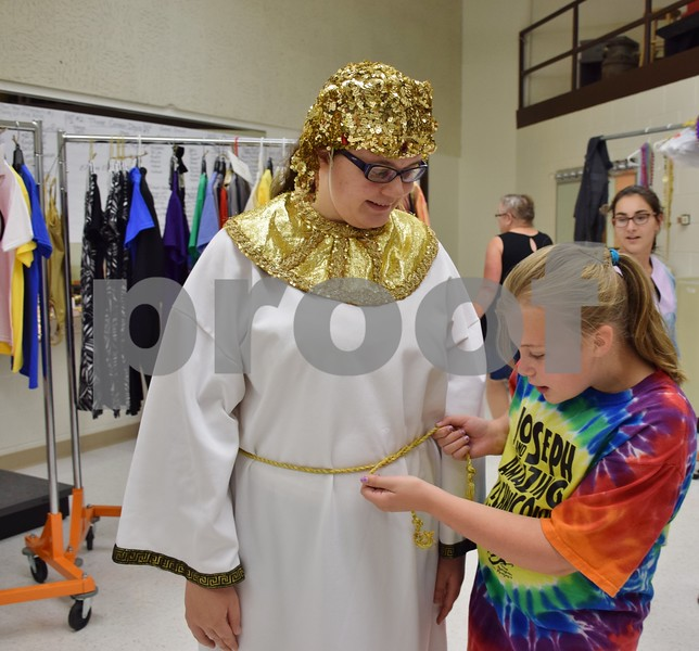 "Before rehearsal on Sept. 22, Piper Schiola-Williams (right) of DeKalb, 10, a mentor with Children's Community Theater's Penguin Project, ties the sash on the Egyptian costume of Lauren Cooper, 15, of Sycamore. Schiola-Williams and Cooper will perform in CCT's Penguin Project's ""Joseph and the Amazing Technicolor Dreamcoat"" at Sycamore High School this weekend."