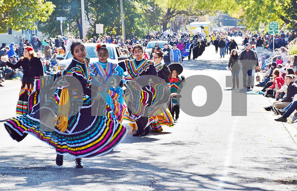 Dancers from Conexión Comunidad wear Dia de los Muertos (Day of the Dead) face paint and traditional clothing while dancing during the 56th annual Sycamore Pumpkin Festival Parade on Sunday.