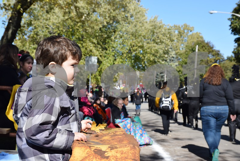 Four-year-old Christian Therapos of Sycamore watches as the DeKalb High School Marching Barbs pass by during the 56th annual Sycamore Pumpkin Festival Parade. The Marching Barbs won first place in their class in the parade.