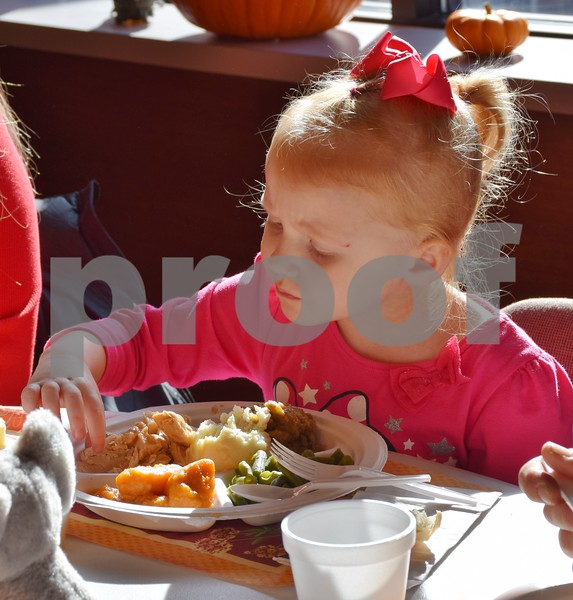 Elyce Smith of Sycamore, 4, eats a plate of food during the free community Thanksgiving dinner Sunday at the Evangelical Lutheran Church of St. John in Sycamore.