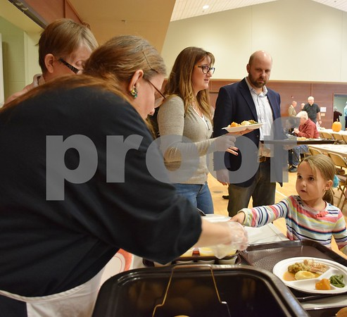 Brenda Campbell (left) helps 6-year-old Lillian Fredrickson, both of Sycamore, choose a roll during the free community Thanksgiving dinner Sunday at the Evangelical Lutheran Church of St. John in Sycamore.