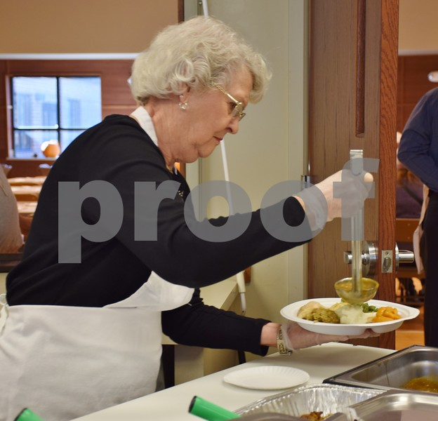 Eilene Ehrhardt of DeKalb pours gravy onto a plate of food during Sunday's free community Thanksgiving dinner at the Evangelical Lutheran Church of St. John, 26555 Brickville Road in Sycamore.