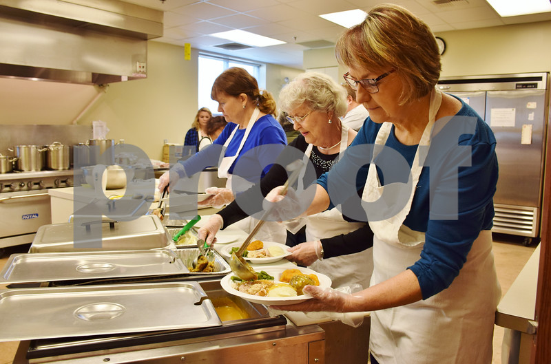 Volunteers with the Evangelical Lutheran Church of St. John, 26555 Brickville Road in Sycamore, help serve plates of food during the free community Thanksgiving dinner on Sunday. Pictured (from left) are Mary Jo Metzger of Rochelle, Eilene Ehrhardt of DeKalb and Lisa Weinhold of Sycamore.