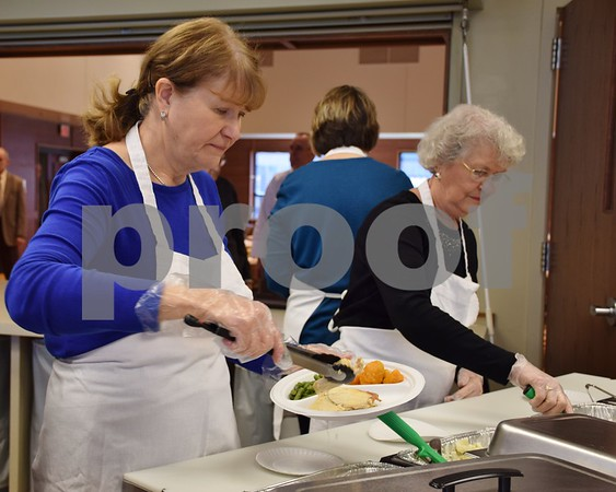 Volunteers with the Evangelical Lutheran Church of St. John, 26555 Brickville Road in Sycamore, help serve plates of food during the free community Thanksgiving dinner on Sunday. Pictured (from left) are Mary Jo Metzger of Rochelle and Eilene Ehrhardt of DeKalb.