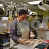 "Ronda Toepper, day care cook at Voluntary Action Center, prepares chicken while Derek Gary, senior meal chef, walks behind her carrying a tray full of food. Toepper describes work as ""dancing around."" As she makes lunches for local preschools, any number of the 15 kitchen workers, including chefs, the dishwasher and Meals on Wheels drivers, can pass in front of, next to or behind her, carrying trays, pots and pans or food."
