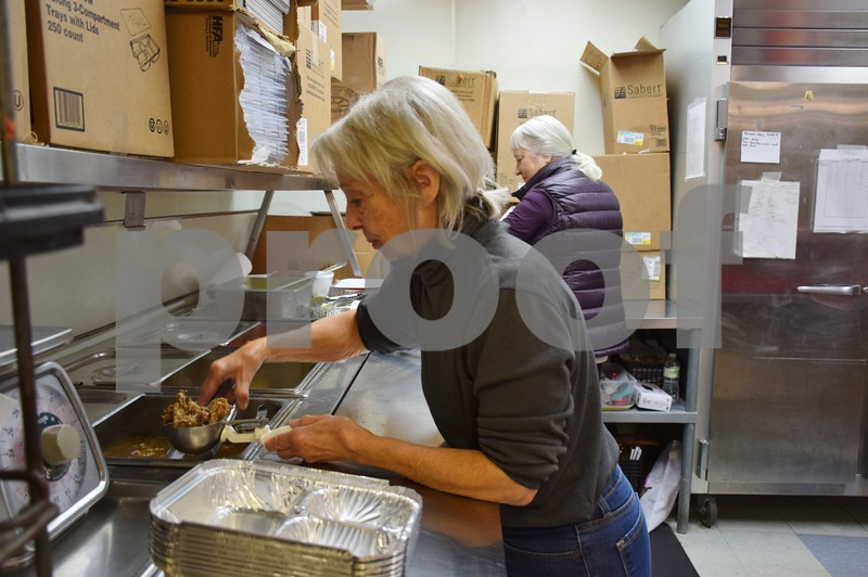 Inside the 2,000-square-foot kitchen at Voluntary Action Center, 1606 Bethany Road in Sycamore, part-time volunteers Mary Alessi of Genoa (left) and Adrienne Soroka of DeKalb make plates of Italian beef, french fries and stewed tomatoes for Meals on Wheels. VAC provides an average of 200 meals a day for the program.