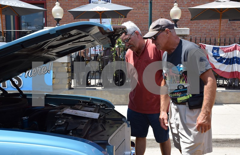 Katrina J.E. Milton - kmilton@shawmedia.com<br /> Best friends Ron Byall of Chicago and Mike Cater of Lake Zurich look under the hood of a 1971 Oldsmobile Cutlass SX owned by Joella Krause of Geneseo on Sunday during the 18th annual Fizz Ehrler Memorial Turning Back Time Car Show.