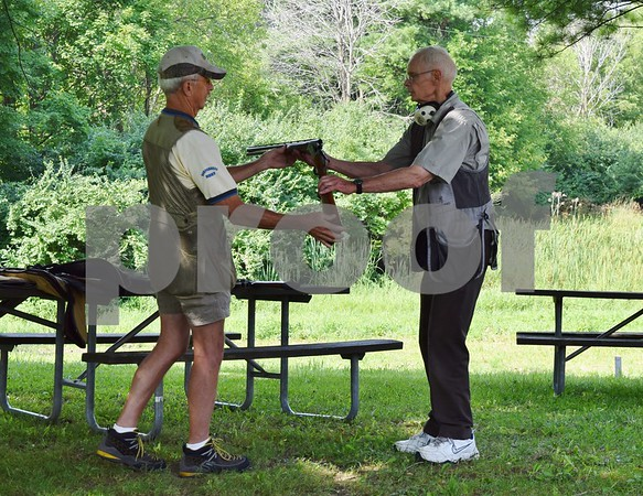 Katrina J.E. Milton - kmilton@shawmedia.com<br /> Chief wingshooting instructor Terry Musser (left) and coordinating instructor Richard Carlson demonstrate how to correctly hand another person an unloaded gun during the Shabbona Lake Youth and Women's Wingshooting Clinic on Aug. 20.