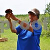 Katrina J.E. Milton - kmilton@shawmedia.com<br /> Illinois Department of Natural Resources instructor Nancy Donaldson demonstrates when and where to aim to hit a clay pigeon during the Shabbona Lake Youth and Women's Wingshooting Clinic on Aug. 20. The introductory clinics taught boys, girls and women interested in learning to shoot or in improving their ability to shoot a shotgun at moving clay targets.
