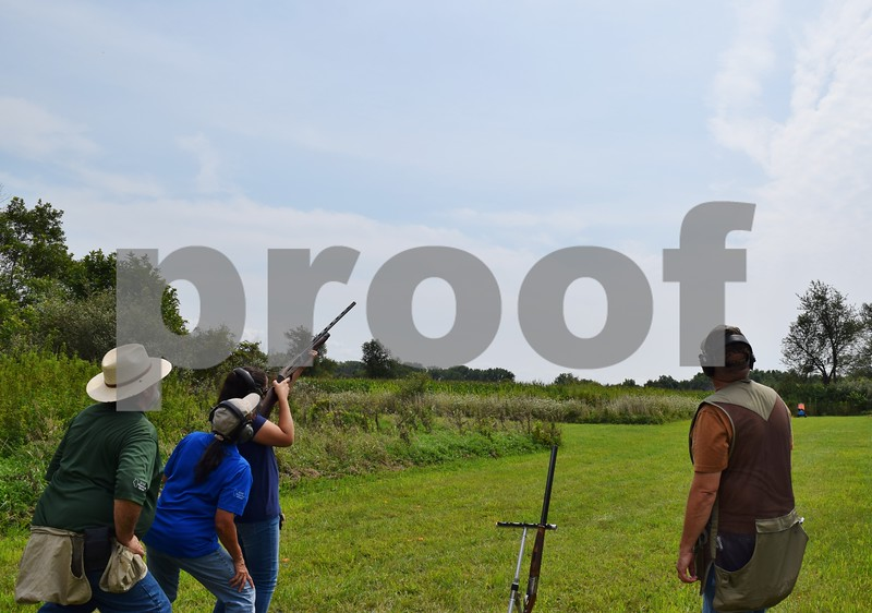 Katrina J.E. Milton - kmilton@shawmedia.com<br /> Misty Underhill of Algonquin shoots a clay pigeon with a 28-gauge semi-automatic shotgun on Aug. 20, during the Shabbona Lake Youth and Women's Wingshooting Clinic. She is pictured (from left) with Illinois Department of Natural Resources coordinating instructor Rod Campbell, instructor Nancy Donaldson and instructor candidate Ed Anderson.