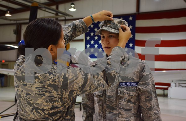 Katrina J.E. Milton - kmilton@shawmedia.com<br /> DeKalb County Composite Civil Air Patrol Squadron Cadet Commander Angeline Tolliver of DeKalb, 17, (left) adjusts the cap of Cadet Blake Starzyk of DeKalb, 14, during a meeting on Sept. 8 at DeKalb Taylor Municipal Airport.