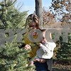 Carly Mondane and her 1-year-old daughter Luella Frantonius of Chicago look a branch on the tree they chose to cut down at the Camelot Christmas Tree Farm in DeKalb on Sunday. Mondane's father, Frank Mondane, and her boyfriend David Frantonius also came from Chicago to find a tree.