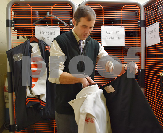 Band Director Steve Lundin examines one of the DeKalb Marching Barbs' uniforms in the school's band supply room. Most of the heavy wool uniforms have tears at seams, pilling from where equipment rubs, missing buttons and irremovable stains. Pants have countless hemlines, broken zippers and worn-out leg bottoms.