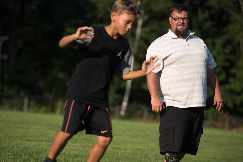 A coach watches one of the kids perform a drill  at the Mike Austin Memorial Football Camp which is free to all boys and girls between the ages of 5 and 14 at the Leominster Pop Warner football field on July 31, 2017.  Mike Austin passed away earlier this year leaving behind 35 plus years of dedication to a number of youth athletic programs in Leominster.  SENTINEL & ENTERPRISE JEFF PORTER