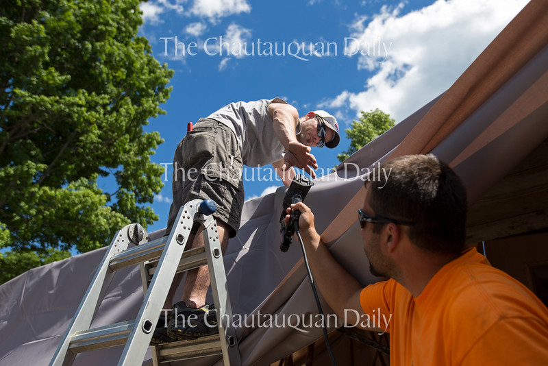 Scott Vincent hands Joe Evans a staple gun while they install an awning Tuesday, June 21, 2016, behind the Amphitheater. The rear of the Amp has been demolished and temporary structures will be used this season before the Amp is rebuilt.