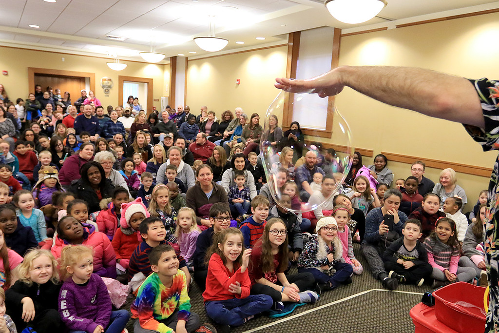 . Mike Dorval of Northboro known as Mike the Bubbleman visited the Leomisnter Public Library on Saturday, January 5, 2019 to a packed house of kids and parents. Everyone watches as he hangs a bubble from his hand during his show. SENTINEL & ENTERPRISE/JOHN LOVE