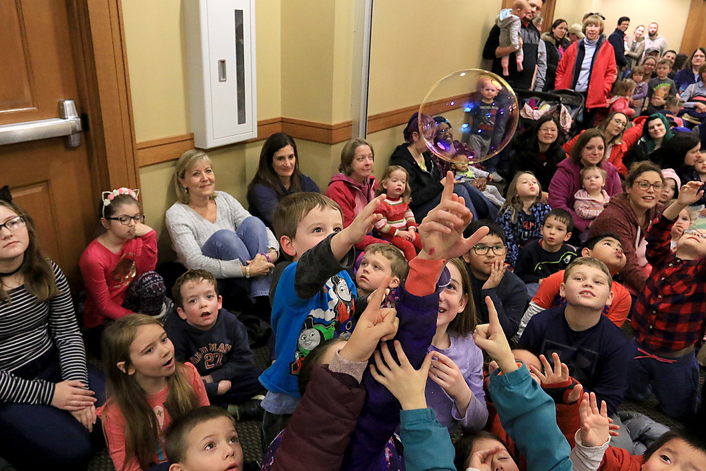 . Mike Dorval of Northboro known as Mike the Bubbleman visited the Leomisnter Public Library on Saturday, January 5, 2019 to a packed house of kids and parents. Kids reach for a bubble as it passes over them during the show. SENTINEL & ENTERPRISE/JOHN LOVE