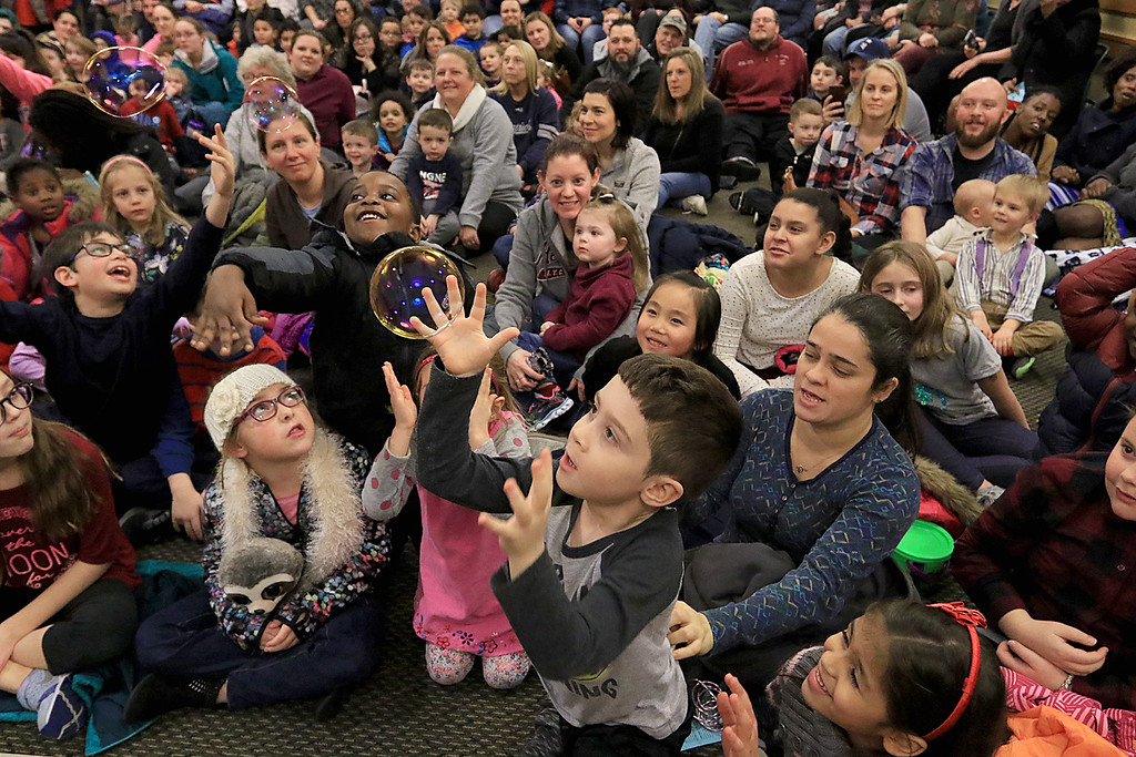 . Mike Dorval of Northboro known as Mike the Bubbleman visited the Leomisnter Public Library on Saturday, January 5, 2019 to a packed house of kids and parents. Marcos Silva, 6, reaches for a bubble during the show. SENTINEL & ENTERPRISE/JOHN LOVE