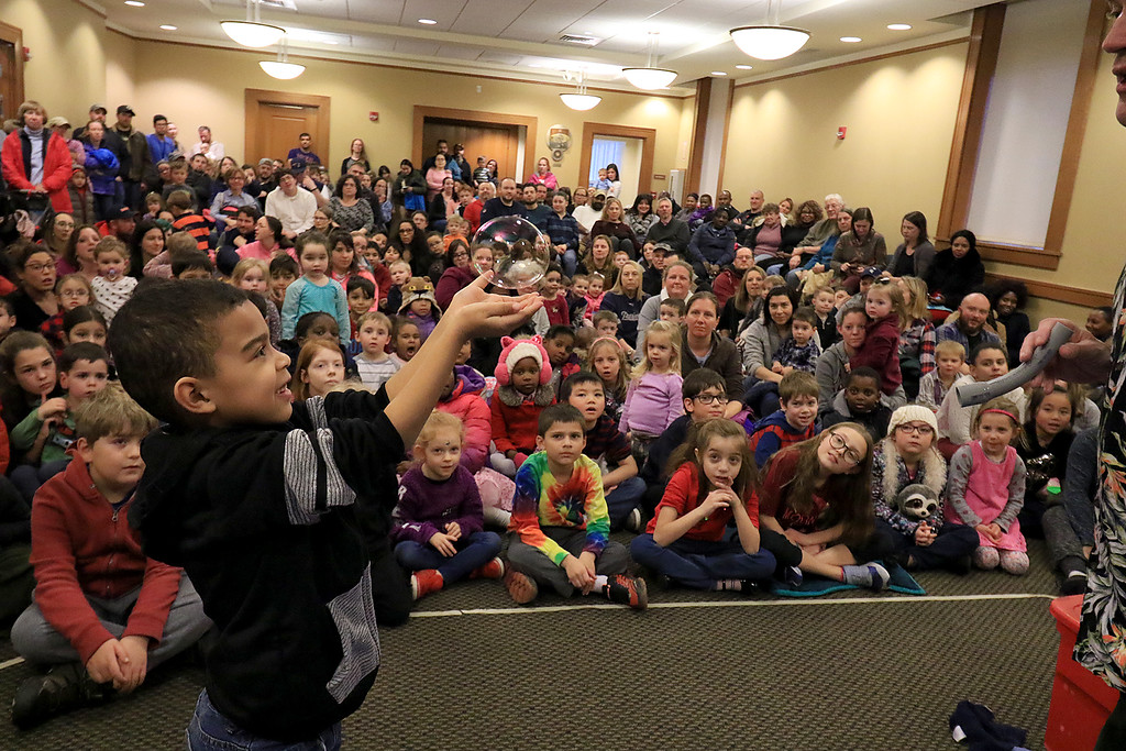 . Mike Dorval of Northboro known as Mike the Bubbleman visited the Leomisnter Public Library on Saturday, January 5, 2019 to a packed house of kids and parents. Syier Faison, 6, of Fitchburg tries to catch a bubble without popping it during the show. SENTINEL & ENTERPRISE/JOHN LOVE