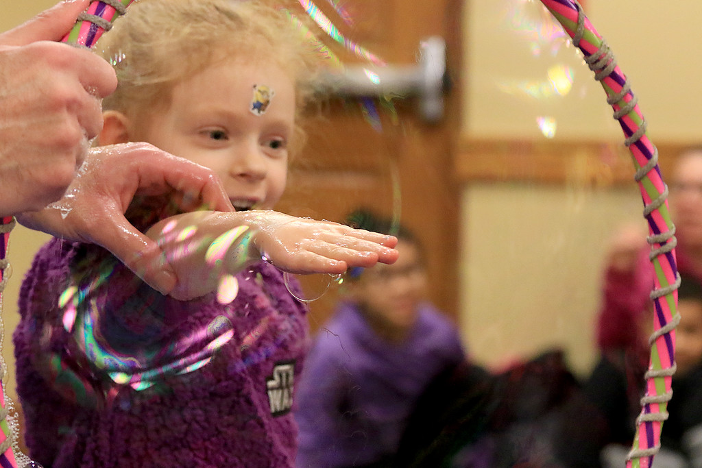 . Mike Dorval of Northboro known as Mike the Bubbleman visited the Leomisnter Public Library on Saturday, January 5, 2019 to a packed house of kids and parents. An young audience member puts her hand through some soap film without popping it during thee show. SENTINEL & ENTERPRISE/JOHN LOVE