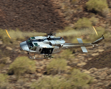A UH-1N Huey maneuvers through the mountains prior to attacking targets during Weapons and Tactics Instructor course 2-07.  The Huey is supporting a heliborne raid during the FINEX phase of training in WTI.