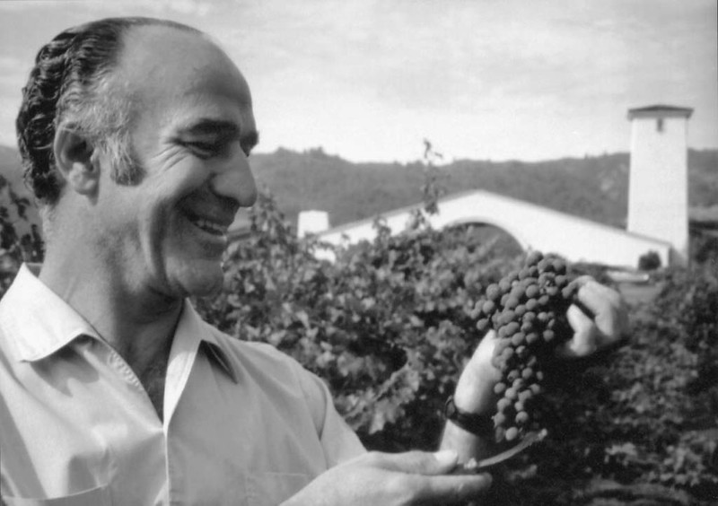 Caption: Napa Valley wine legend Robert Mondavi with his namesake winery's iconic arch and tower in the background.
