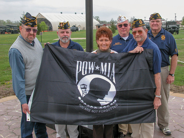 Members of Edinburgh Legion Post 233 and Fighting Seventh District representatives present a new POW flag to be flown over the static military hardware display just outside the gates of Camp Atterbury.